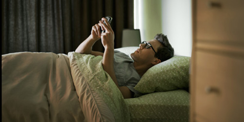 08 Feb 2011 --- Man checking cell phone in bed --- Image by © Tim Pannell/Corbis